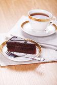 テーブルをにてお茶を一杯とチョコレート ケーキのスライス — ストック写真