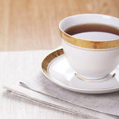 A cup of tea on a table on linen napkin — Stock Photo