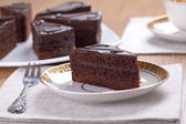 Slice of chocolate cake with a cup of tea served on a table — Stock Photo