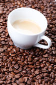 White cup of coffee on coffee beans background — Stock Photo