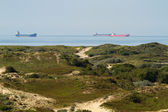 Industrial ships on sea with dunes — Stock Photo