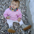 Baby girl beach pebbles — Stock Photo