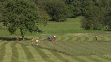 Granjero hace balas de heno con un tractor — Vídeo de Stock