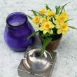 Narcissuses a vase an ashtray — Stock Photo