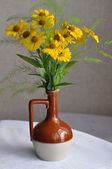 Bunch of yellow flowers in a jug — Stock Photo