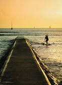 Waikiki pier and paddleboarding man — Stock Photo
