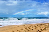 Rainbow over beach — Stock Photo