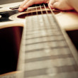 Macro shot down the fretboard of acoustic guitar with shallow depth of field - Стоковая фотография