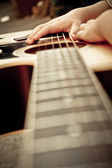 Macro shot down the fretboard of acoustic guitar with shallow depth of field — Stock Photo