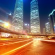 Light trails on modern building background in shanghai china. — Stock Photo #13604530