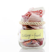 A lot of money in a glass bottle labeled :College fund — 图库照片
