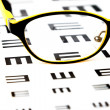 Stock Photo: Glasses on vision test chart