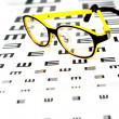 Glasses on vision test chart - Stock Photo