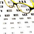 Glasses on vision test chart — Stock Photo