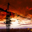 Industrial construction cranes and building silhouettes over sun at sunrise. — Stock Photo #27158011