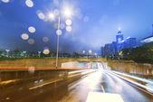 Tráfico con desenfoque ligero a través de la ciudad por la noche — Foto de Stock
