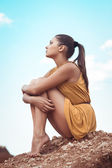 Swarthy brunette girl sitting on a rock — Stock Photo