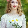 Young beautiful woman with a bouquet of daisies in the park — Stock Photo