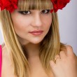 Studio portrait of a beautiful young blonde woman with a rim of red roses large — Stock Photo #36802651