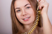 Portrait of beautiful young brown-haired woman without makeup in a necklace with yellow stones — Stock Photo