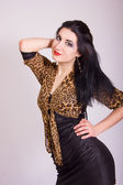 Studio portrait of a beautiful slim brunette girl in a short tight black dress with leopard bolero — Stock Photo