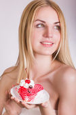 Portrait of a beautiful young blonde woman in the studio on a white background. Girl posing in a beautiful dress with a cake in the shape of heart. — Stock Photo