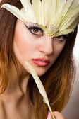 Portrait of beautiful young brown-haired woman with long hair in a studio. Makeup with long black arrow and yellow long feathers — Stock Photo