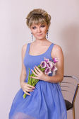 Portrait of a beautiful young blonde girl on a white background in a blue dress. Woman posing with a bouquet of purple tulips. — Stock Photo