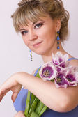 Portrait of a beautiful young blonde girl on a white background in a blue dress. Woman posing with a bouquet of purple tulips. — Stockfoto