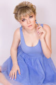 Portrait of a beautiful young blonde woman with short hair and dressed in a blue short dress. Girl posing with different emotions in the studio. — Stok fotoğraf