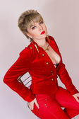 Portrait of a beautiful young blonde girl with short hair in a sexy business style. A woman dressed in a red jacket and red pants. — Стоковое фото