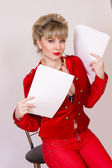 Portrait of a beautiful young blonde girl with short hair in a sexy business style. A woman dressed in a red jacket and red pants. — Stockfoto