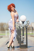 Gorgeous red-haired woman on a walk in the park. Young girl on the nature — Stok fotoğraf