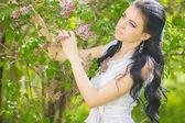 Bella bruna giovane in posa in natura. ragazza con capelli e trucco in abito romantico bianco — Foto Stock