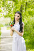 Beautiful young brunette posing in nature. Girl with hair and makeup in white romantic dress — Stock Photo