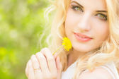 Portrait of a beautiful young blonde woman with dandelions. Girl posing in nature and smiling — Stock Photo