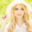 Portrait of a beautiful young blonde woman with wavy hair in nature. Girl in white hat sitting on the grass in the park — Stock Photo #45990113