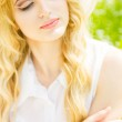 Portrait of a beautiful young blonde woman with wavy hair in nature. Girl in white hat sitting on the grass in the park — Stock Photo #45990205