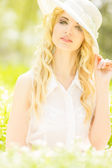 Portrait of a beautiful young blonde woman with wavy hair in nature. Girl in white hat sitting on the grass in the park — Stock Photo
