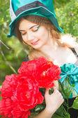 Portret to piękna młoda kobieta w stroju Szalony Kapelusznik w przyrodzie. dziewczyna pozuje z bukietem czerwonych piwonie — Zdjęcie stockowe