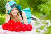 Retrato de una bella mujer joven con un traje del sombrerero loco en la naturaleza. chica posando con un ramo de peonías rojas — Foto de Stock