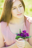 Portrait of a beautiful young woman with brown hair in retro plaid dress. Girl posing in nature with a small bouquet of violets — Stock Photo