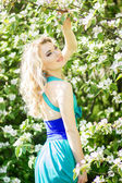 Portrait of a beautiful young blonde woman with long hair in a long blue dress with a high slit in nature. — Stock Photo