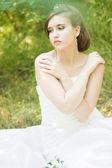 Porträt einer schönen jungen braut in der natur. junge frau hält einen kleinen strauß weiße rosen in der hand — Stockfoto