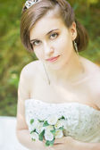 Portrait of a beautiful young bride in nature. Young woman holding a small bouquet of white roses in their hands — Stock Photo