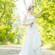 Portrait of a beautiful young bride in nature. Young woman holding a small bouquet of white roses in her hands — Stock Photo #47985109