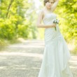 Portrait of a beautiful young bride in nature. Young woman holding a small bouquet of white roses in her hands — Stock Photo