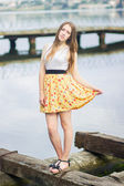 Young woman near the blue water in dress — Stock Photo