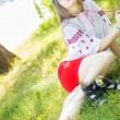 Outdoor portrait young woman with long brown hair. The girl floral accessories, she poses lying on the grass in the park — Stock Photo #50614993