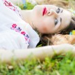 Outdoor portrait young woman with long brown hair. The girl floral accessories, she poses lying on the grass in the park — Stock Photo #50615009